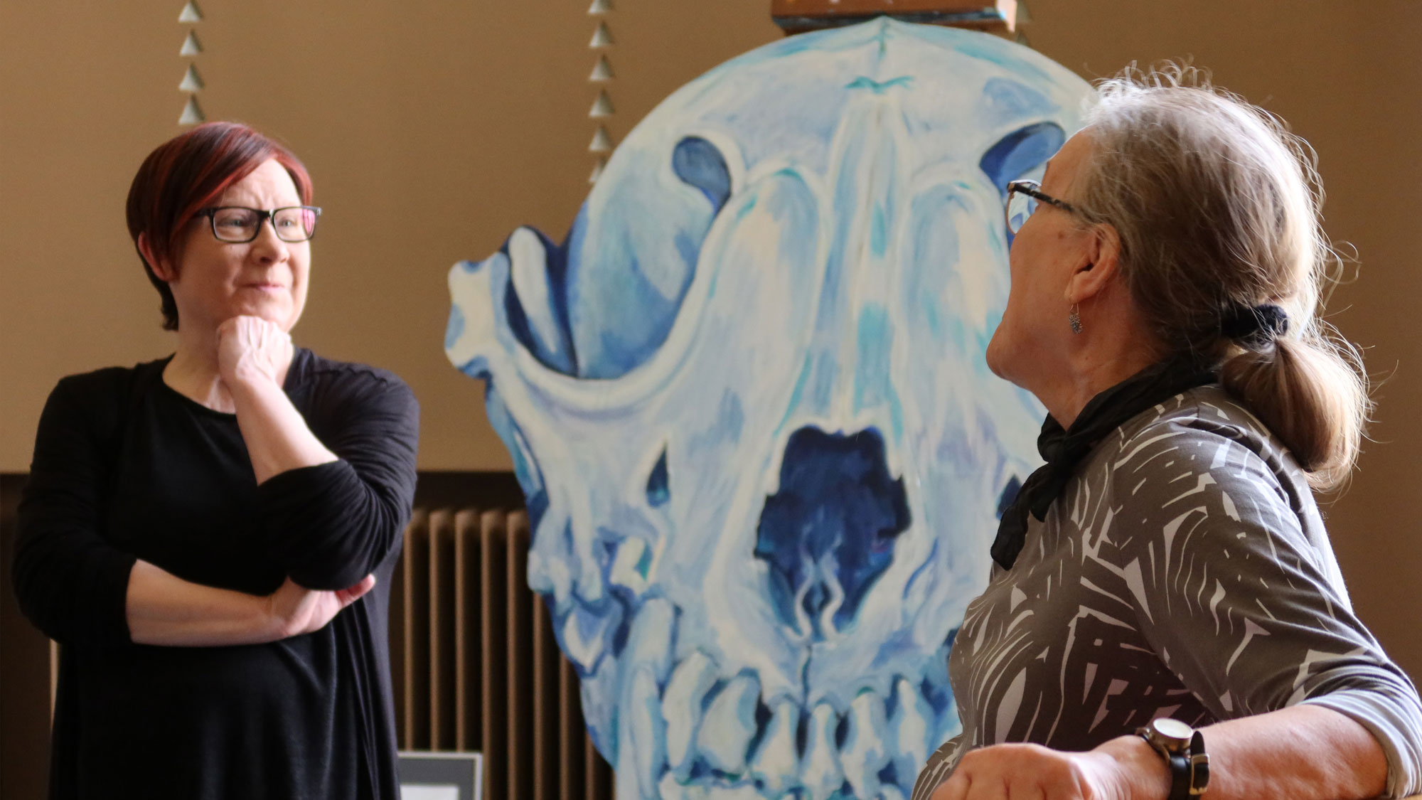 Teatterinjohtaja Iiristiina Varilo ja kuvataiteilija Arja Valkonen-Goldblatt keskustelevat teatterin aulassa. Taustalla sinisävyinen maalaus.